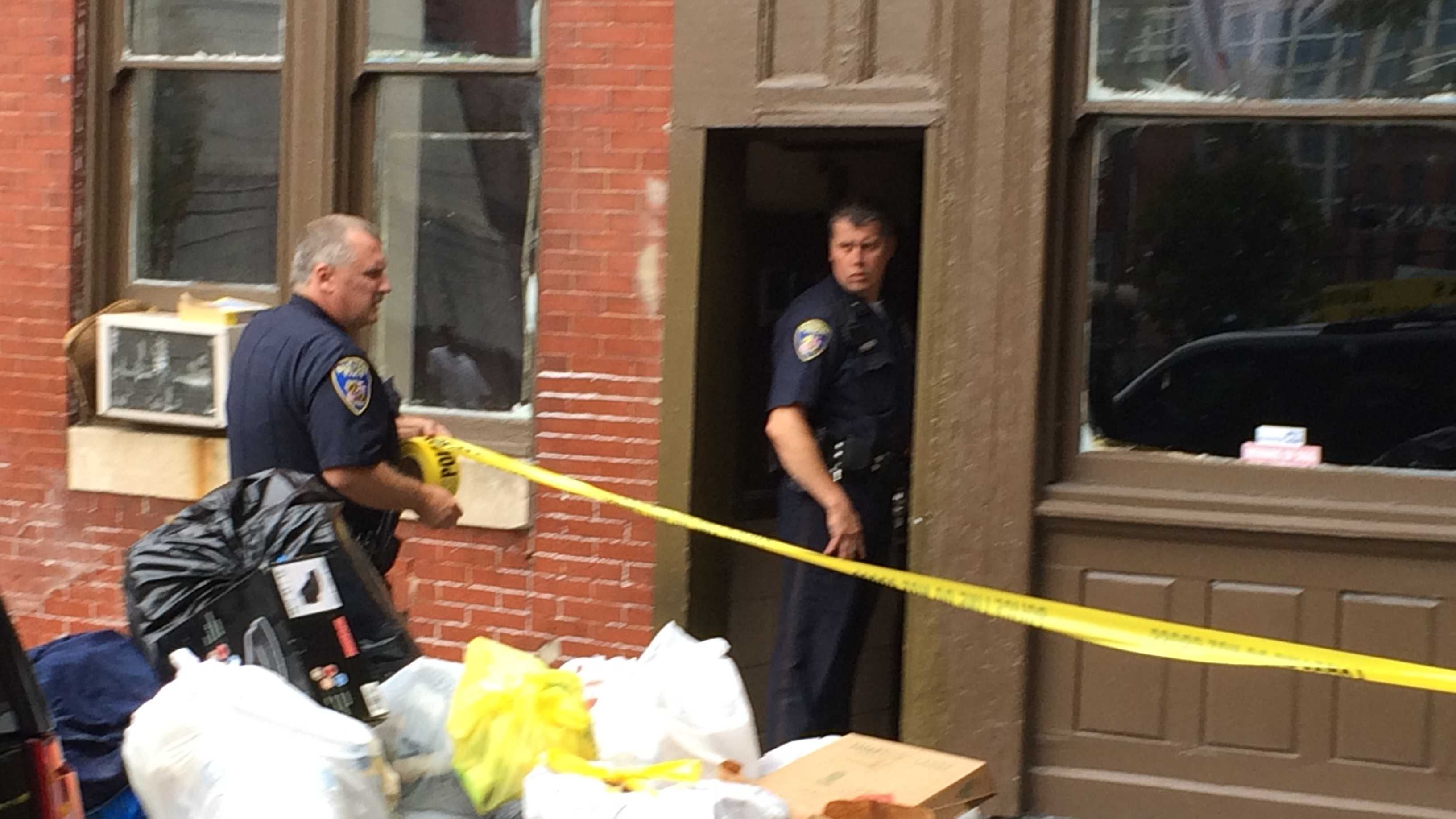 Police put up crime scene tape at the apartment where the woman was found.