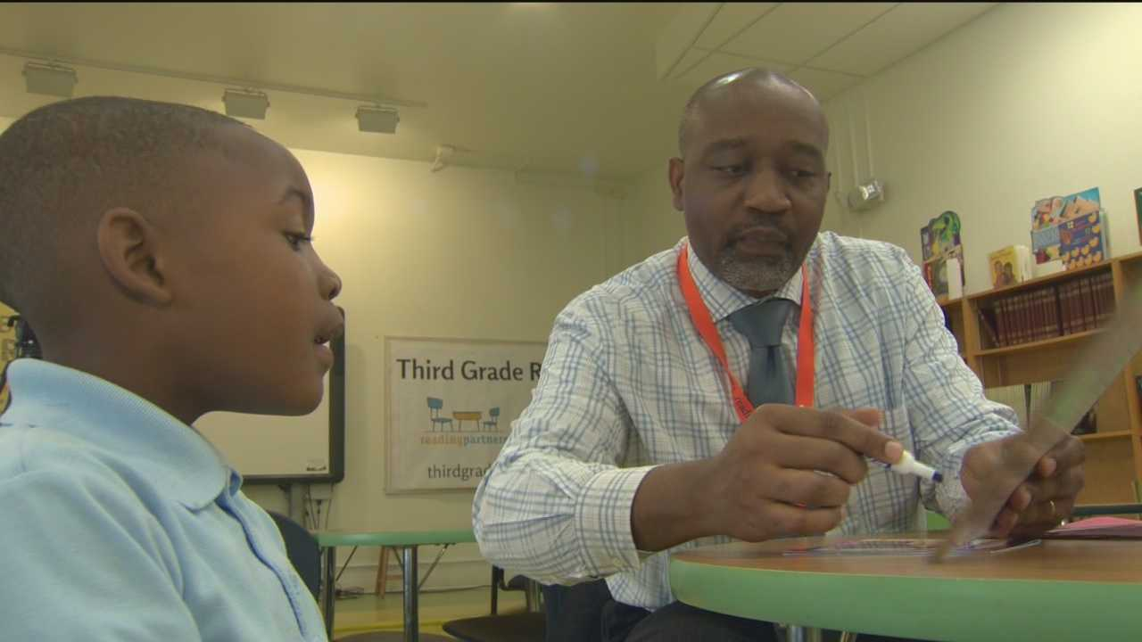 Baltimore City employees volunteer their time to help young school children with reading.