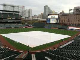 Crews work to maintain Oriole Park on a rainy morning before ALCS Game 1.