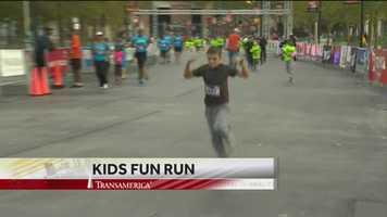The Kids Fun Run winner flexes on his way to the finish line.