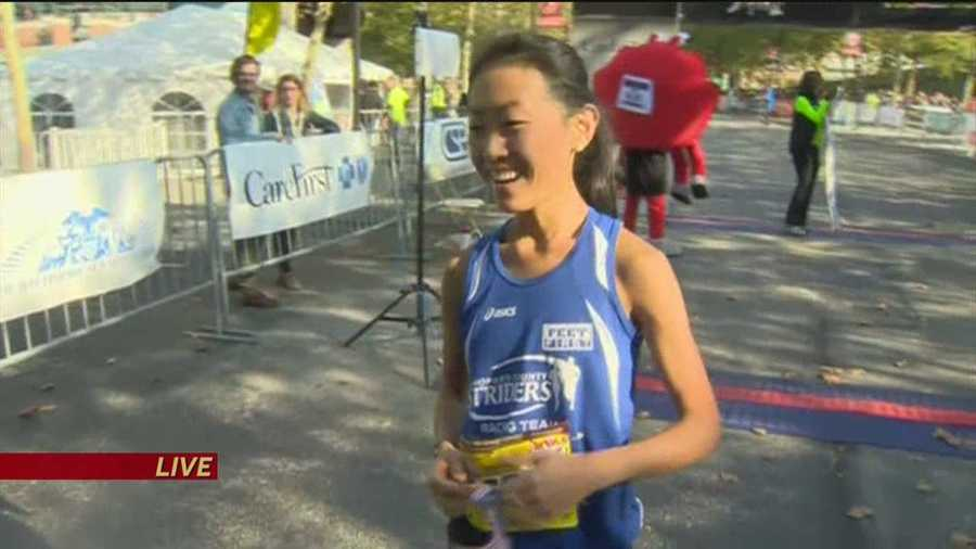 Wang has a big smile as she realizes she's the winner of the women's 2014 Baltimore Marathon.