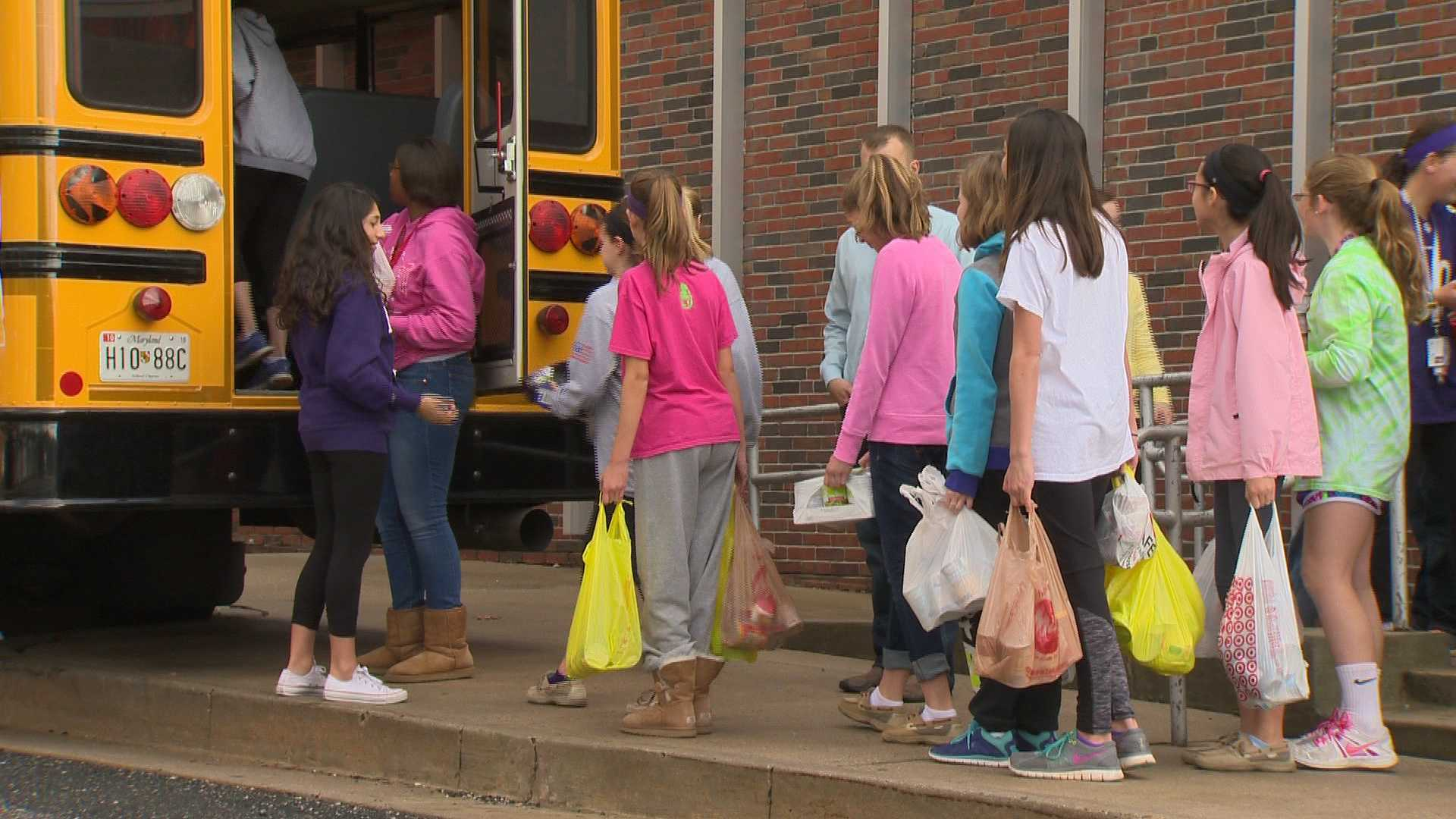 Ridgely Middle School students drop canned goods in a bus for their annual Stuff A Bus campaign.