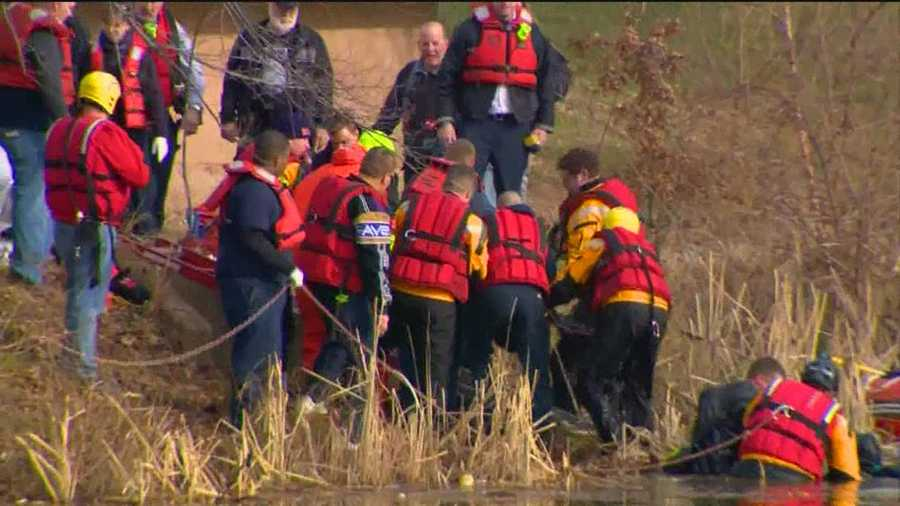 Rescue crews work to pull a child from an icy Lansdowne pond after he and three friends fell into it Sunday.