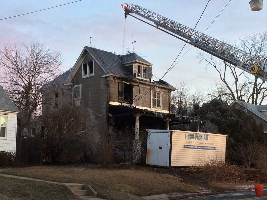 Baltimore County fire officials work to put out hot spots early Friday morning from a fire that killed a woman in Overlea.