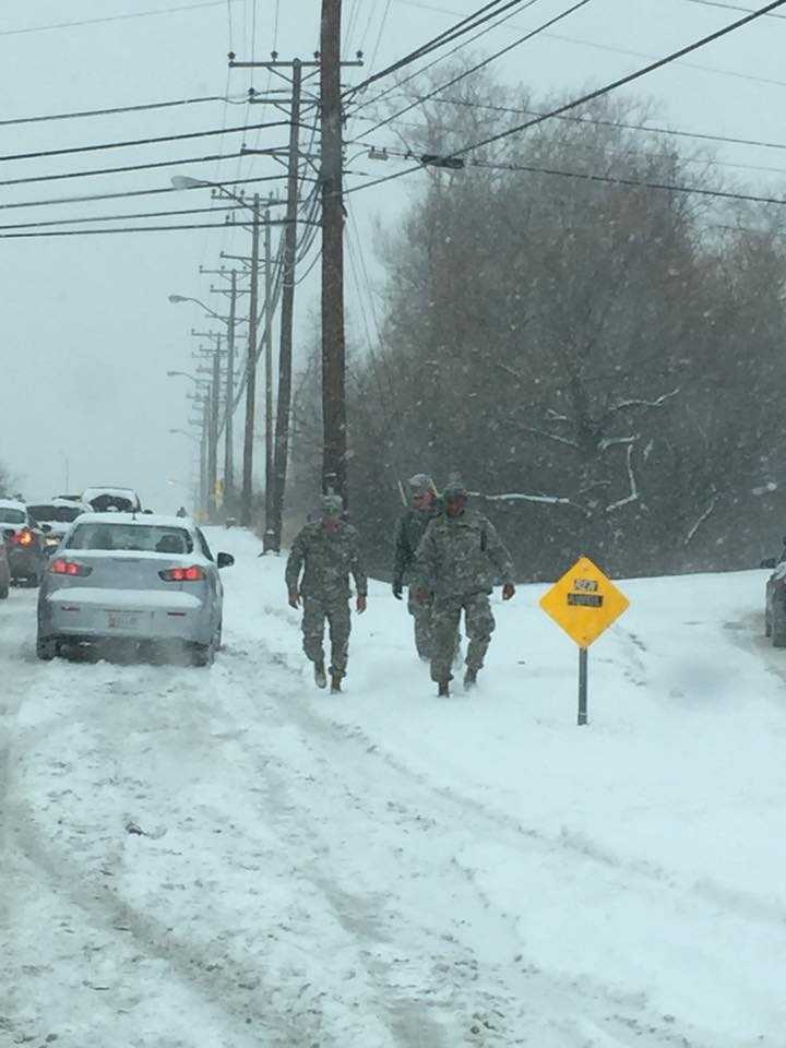 Service members help push cars up hill on Ritchie Highway in Glen Burnie