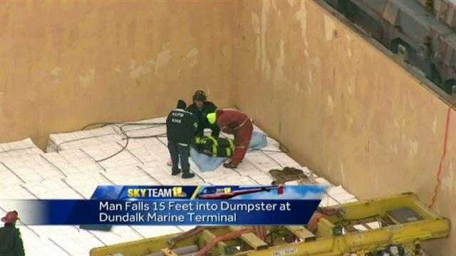 Crews work to rescue the man after he fell into a dumpster on a ship.