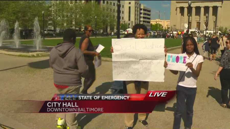 """Students from Digital Harbor High School chanting """"We love Baltimore"""" and carrying signs reading """"Be more noble"""" and """"Be more peaceful"""" march to City Hall."""