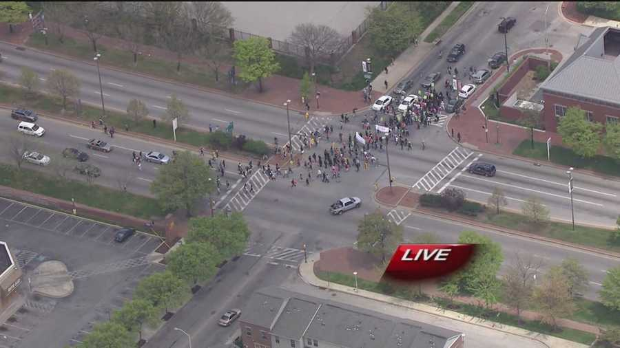 The crowd turns left at Martin Luther King Jr. Boulevard onto Saratoga Street, headed toward City Hall.