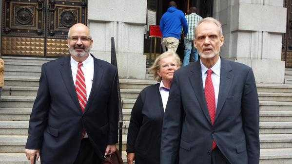 Heather Cook, flanked by her attorneys, leaves court after her trial date is postponed.