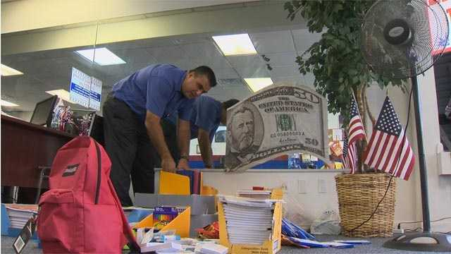 Liberty Tax Service franchise owner Kal Darraj goes through donated schools supplies as part of his Freedom to Learn drive.