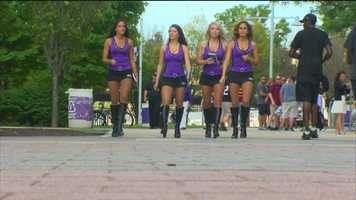 Members of the Ravens cheerleading team walk outside M&T Bank Stadium prior to the team's 2015 preseason opener against the New Orleans Saints.