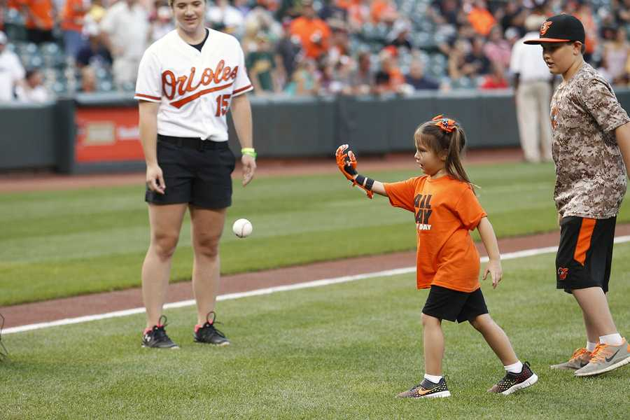 Hailey Dawson, 5, from Las Vegas, got the chance to throw out the ceremonial first pitch prior to Monday's Orioles-A's game thanks to a robotic hand developed by UNLV engineering students.