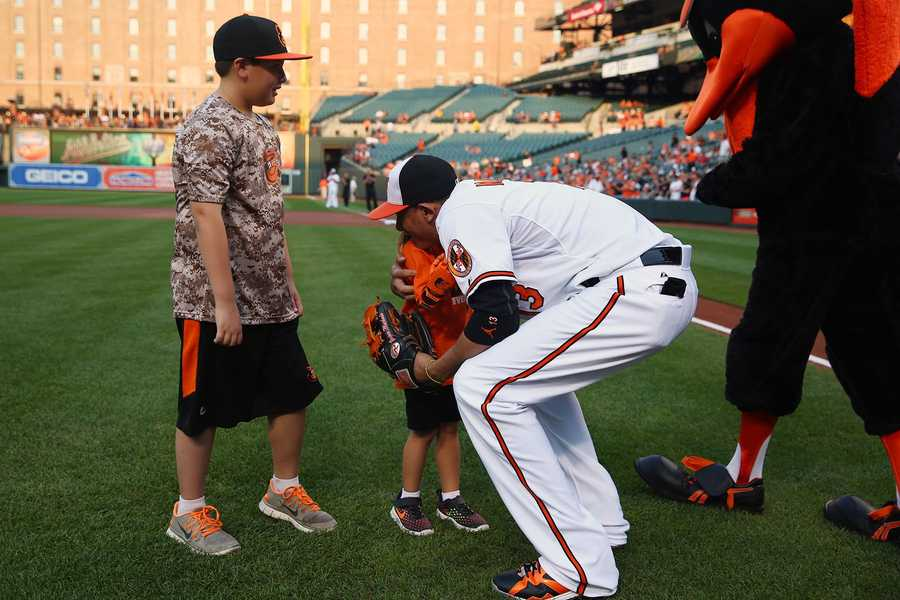 Hailey Dawson, 5, of Las Vegas, gets a hug from Orioles third baseman Manny Machado. Thanks to a robotic hand developed by UNLV students, Hailey was able to throw out the first pitch at Camden Yards.