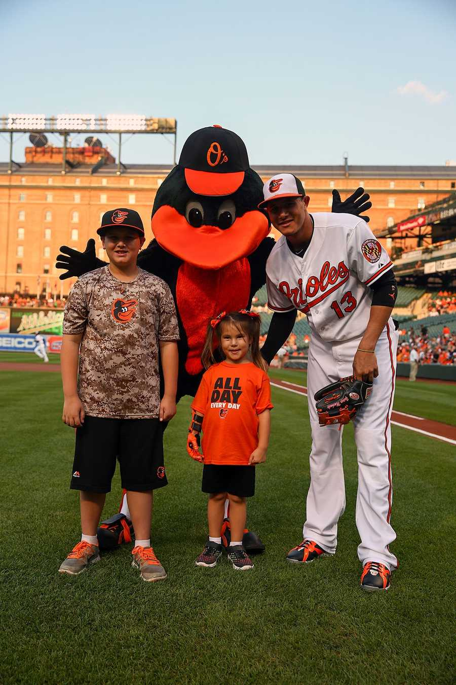 Hailey Dawson, 5, of Las Vegas is joined by the Oriole Bird and third baseman Manny Machado on the day she threw out the first pitch thanks to a robotic hand.