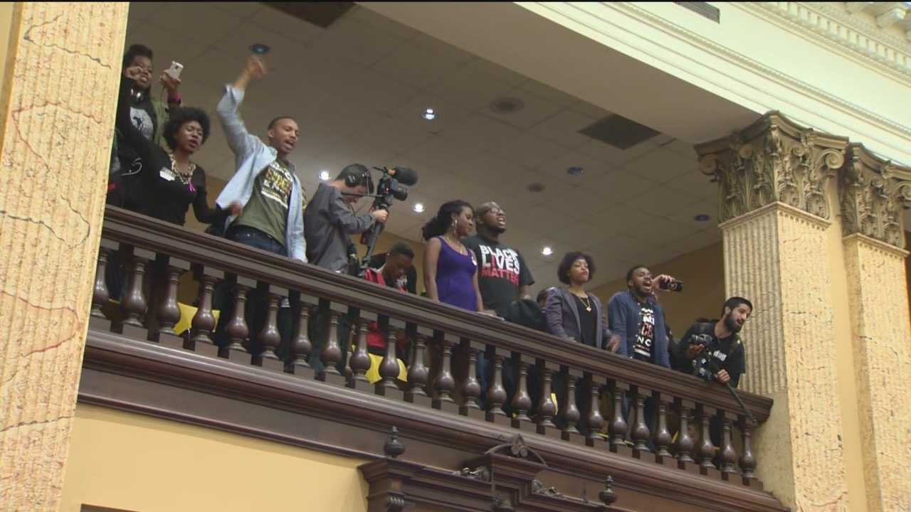 "Baltimore police arrested 16 people for trespassing inside City Hall after a protesters demonstrated at a City Council committee's confirmation hearing for Interim Police Commissioner Kevin Davis. It all started when protesters filled a balcony demanding a voice in the selection of the police commissioner. They tried to stop the vote on confirming Davis as police commissioner, chanting ""No justice, no peace."" While many wonder why police waited so long to make arrests, authorities cited no need to create an"