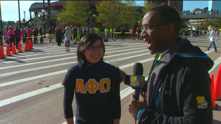WBAL-TV 11 News' Jason Newston speaks to one of the 1,400 volunteers at the Baltimore Running Festival.