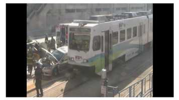 Emergency crews seek to rescue two people trapped after their vehicle collided with a light rail train near the Baltimore Convention Center.