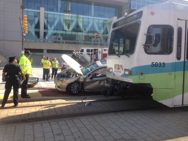 Two people were trapped in a car after their vehicle collided with a light rail train near the Baltimore Convention Center.