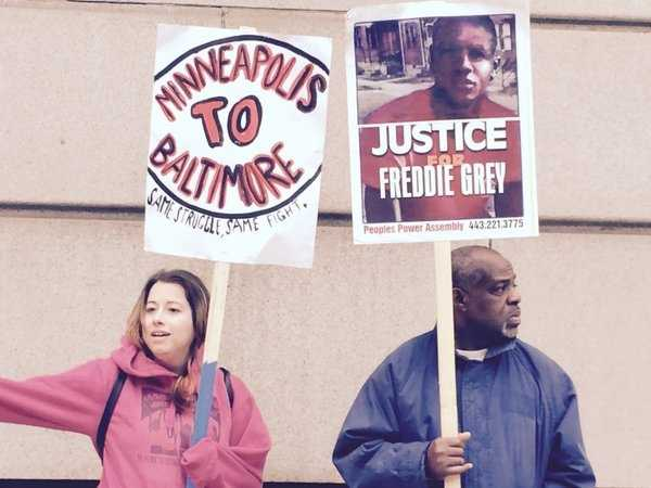Protesters hold up signs in support of Freddie Gray as the trial of Officer William Porter gets upderway