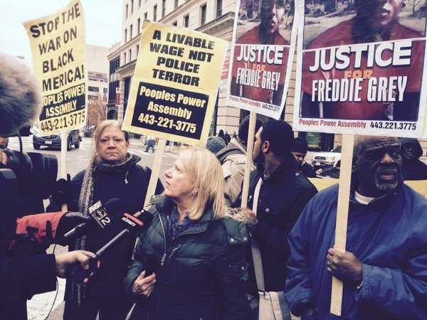 Protesters speak to the media as the trial of Officer William Porter gets underway.