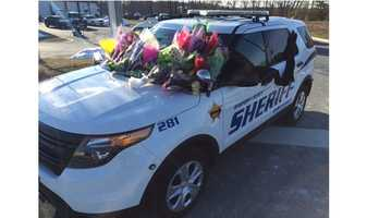 Flowers were placed on a Harford County Sheriff's Department vehicle in tribute to two deputies that were killed in the line of duty Wednesday in Abingdon.
