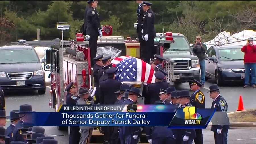 Members of the Joppa Magnolia Volunteer Fire Company help lower the flag-draped coffin of Harford County Sheriff's Office Senior Deputy Patrick Dailey.