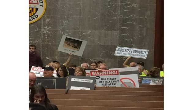 Resident display signs at the March 7 Baltimore County Council meeting to show their concern over what they call a growing rat problem in their communities.