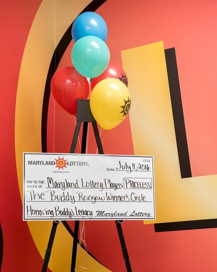 Lottery winners are routinely greeted with applause when they walk into the Buddy Roogow Winner's Circle to claim their prizes. The recently renovated room is festively decorated with the Lottery's red and yellow logo, and the walls are adorned with photos of past winners, many smiling as they pose with oversized novelty checks in hand.