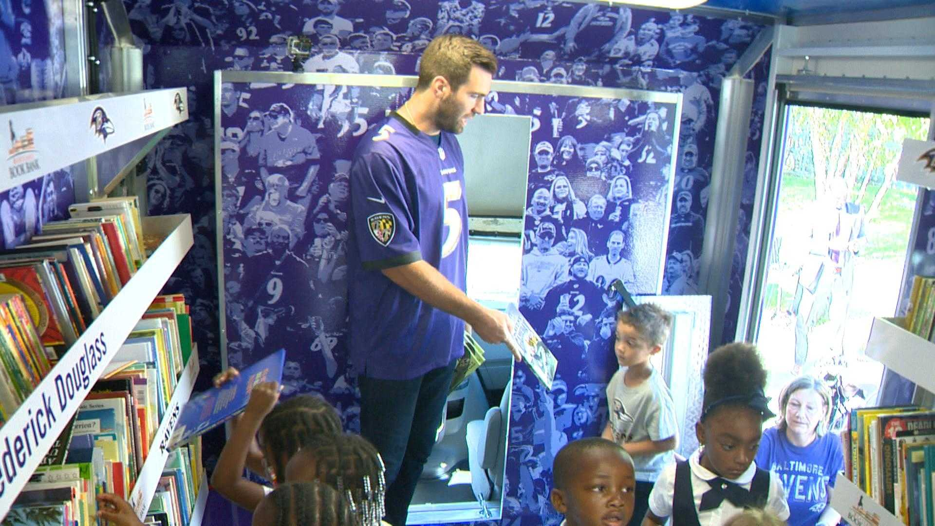 Ravens quarterback Joe Flacco hands out books to children at Abbottston Elementary School as the team unveils its bookmobile.