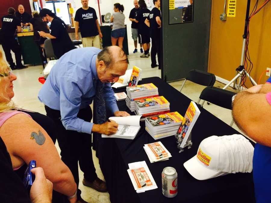 "Pro wrestling journalist Bill Apter signs copies of his book ""Is Wrestling Fixed? I Didn't Know it Was Broken."""