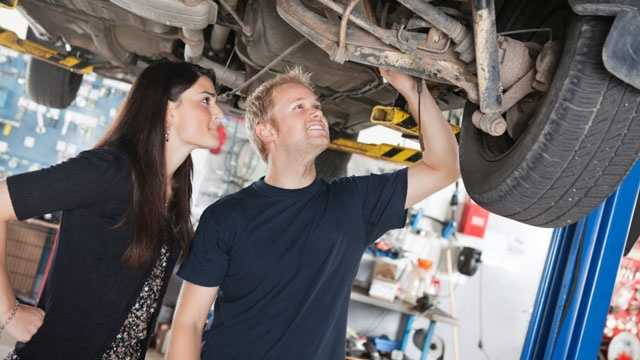 mechanic checking out car with customer