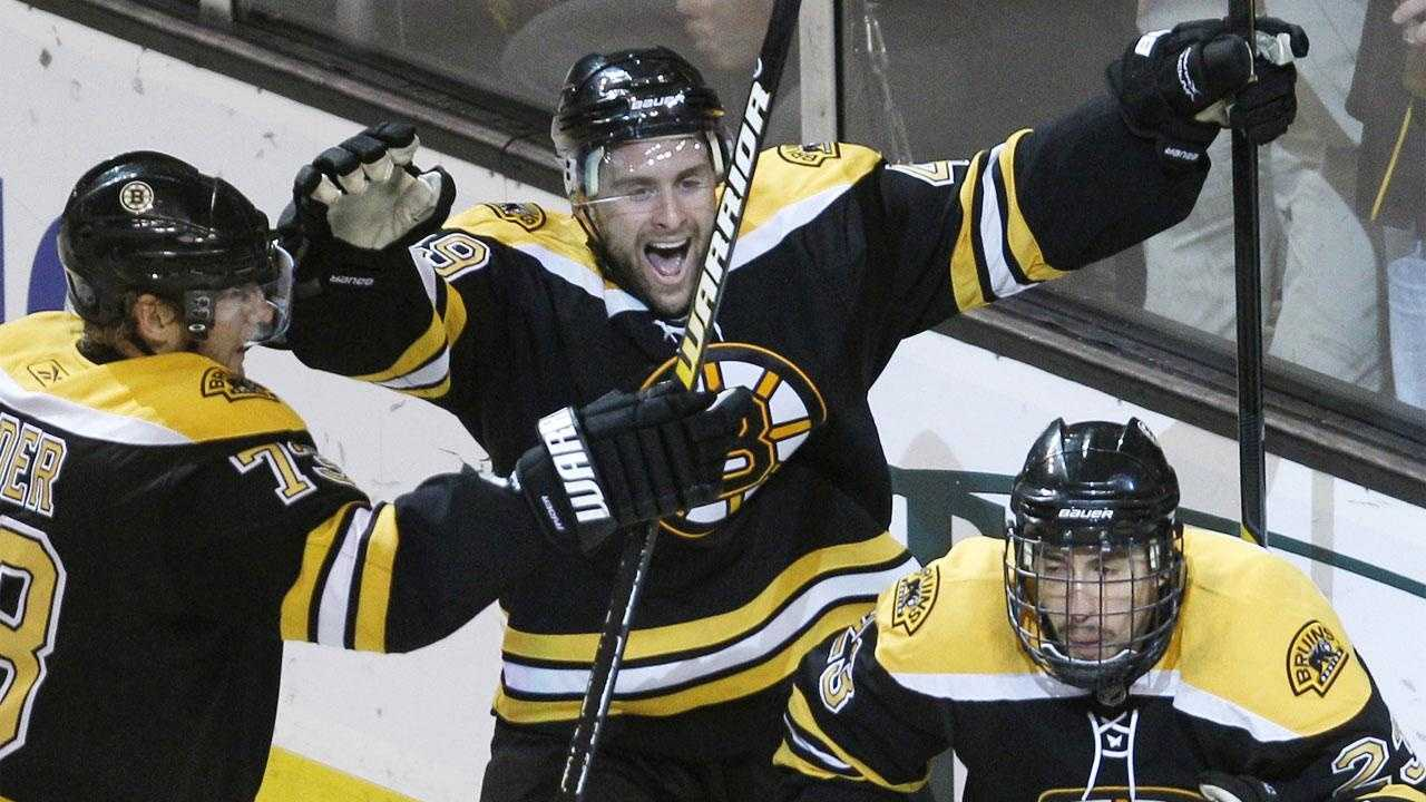 Boston Bruins center Chris Kelly, right, pumps his fist as he is congratulated by teammates Michael Ryder, left, and Rich Peverley after scoring a goal against the Montreal Canadiens during the third period in Game 7.