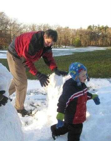 Tom Mortimer making a snowman with his children.