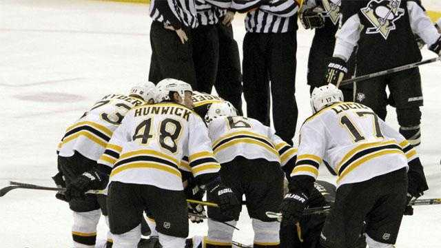 The Boston Bruins lean over fallen teammate Marc Savard after a hit in the third period.