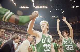 Larry Bird gets a congratulation as teammate Kevin McHale goes up with his arms in victory over the Houston Rockets on June 4, 1986