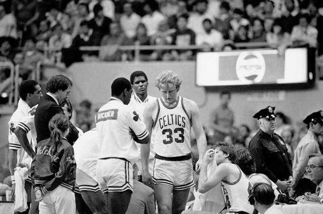 Larry Bird walks to the locker room after re-injuring his ankle during an NBA playoff game against the New York Knicks on April 30, 1984.
