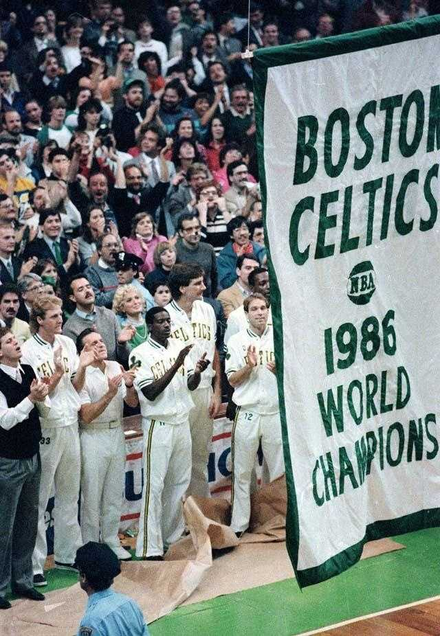 The Boston Celtics applaud as a banner celebrating the Celtics 1986 NBA World Championship title is lifted to the roof of Boston Garden on Oct. 31, 1986.