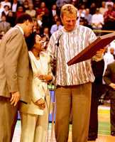 Dennis Johnson and Larry Bird present Donna Harris-Lewis, the widow of former Boston team captain Reggie Lewis, with a gift during a ceremony where Lewis' number was retired.
