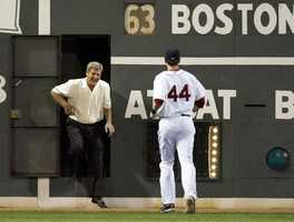 "Bobby Orr, of Canada, emerges from the left field ""Green Monster"" wall to greet Jason Bay, also of Canada, during the seventh-inning stretch at Fenway Park on June 17, 2009."