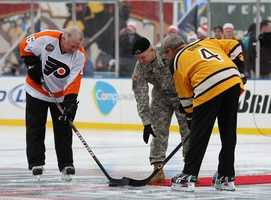 Staff Sgt. Ryan LaFrance drops the ceremonial first puck for Bobby Clarke and Bobby Orr during the Winter Classic at Fenway Park on Jan. 1, 2010