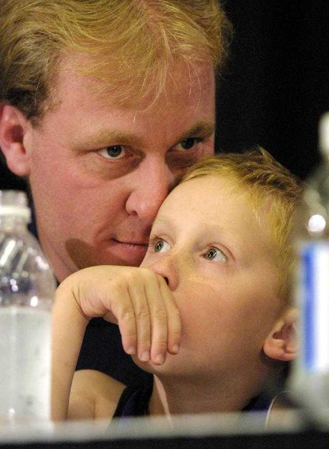 Schilling nuzzles his six-year-old son Gehrig during a press conference in November 2001