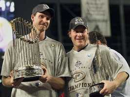 World Series co-MVPs Arizona Diamondbacks pitchers Randy Johnson and Schilling hold the World Series winner's trophy and the MVP trophy after the Diamondbacks win of Game 7 of the World Series in 2001.