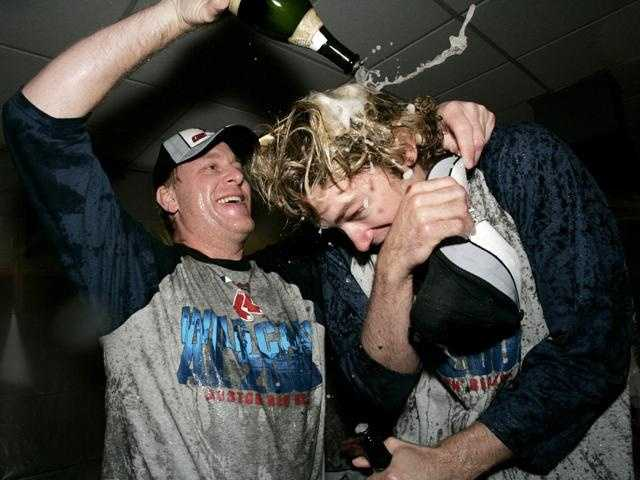 Schilling pours champagne over teammate Bronson Arroyo in the locker room after their team defeated the Yankees to clinch the wildcard spot in 2005.