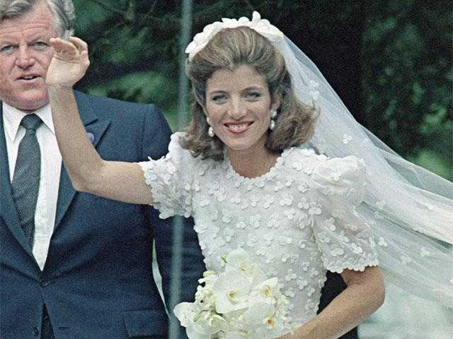 Caroline waves as she leaves the church, with her uncle Ted Kennedy.