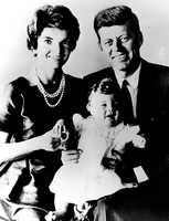 Sen. John F. Kennedy poses with his wife Jacqueline, and their 11-month-old daughter Caroline, during a visit to Hyannisport, October 4, 1958.