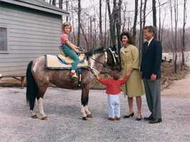 Caroline Kennedy sits atop a pony while her parents and brother look on, March 31, 1963.