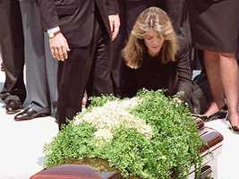 Caroline Kennedy Schlossberg kneels at the foot of her mother's casket, May 23, 1994.