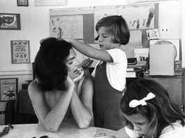 Caroline Kennedy runs her hand through her mother's hair during a visit to Caroline's school on May 24, 1962.