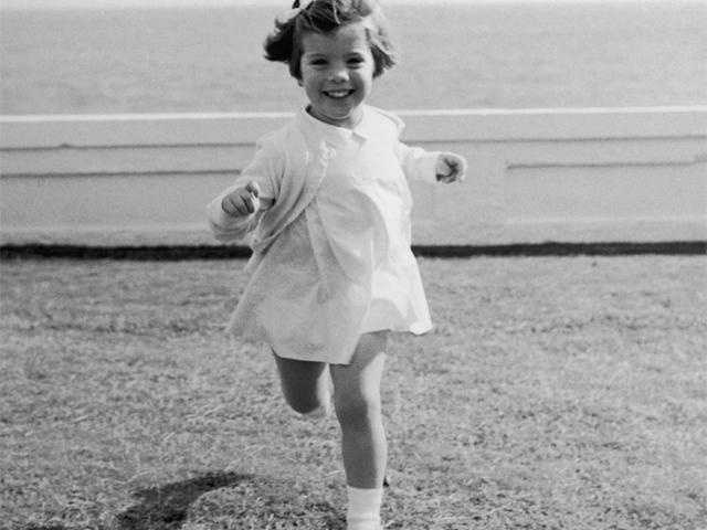 Caroline Kennedy running on a lawn during a family vacation in Palm Beach, Florida in 1961.