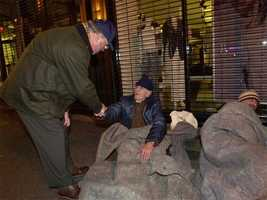 Menino shakes hands with a homeless man who, along with his son, sleeps under blankets on a sidewalk, Dec. 10, 2001.
